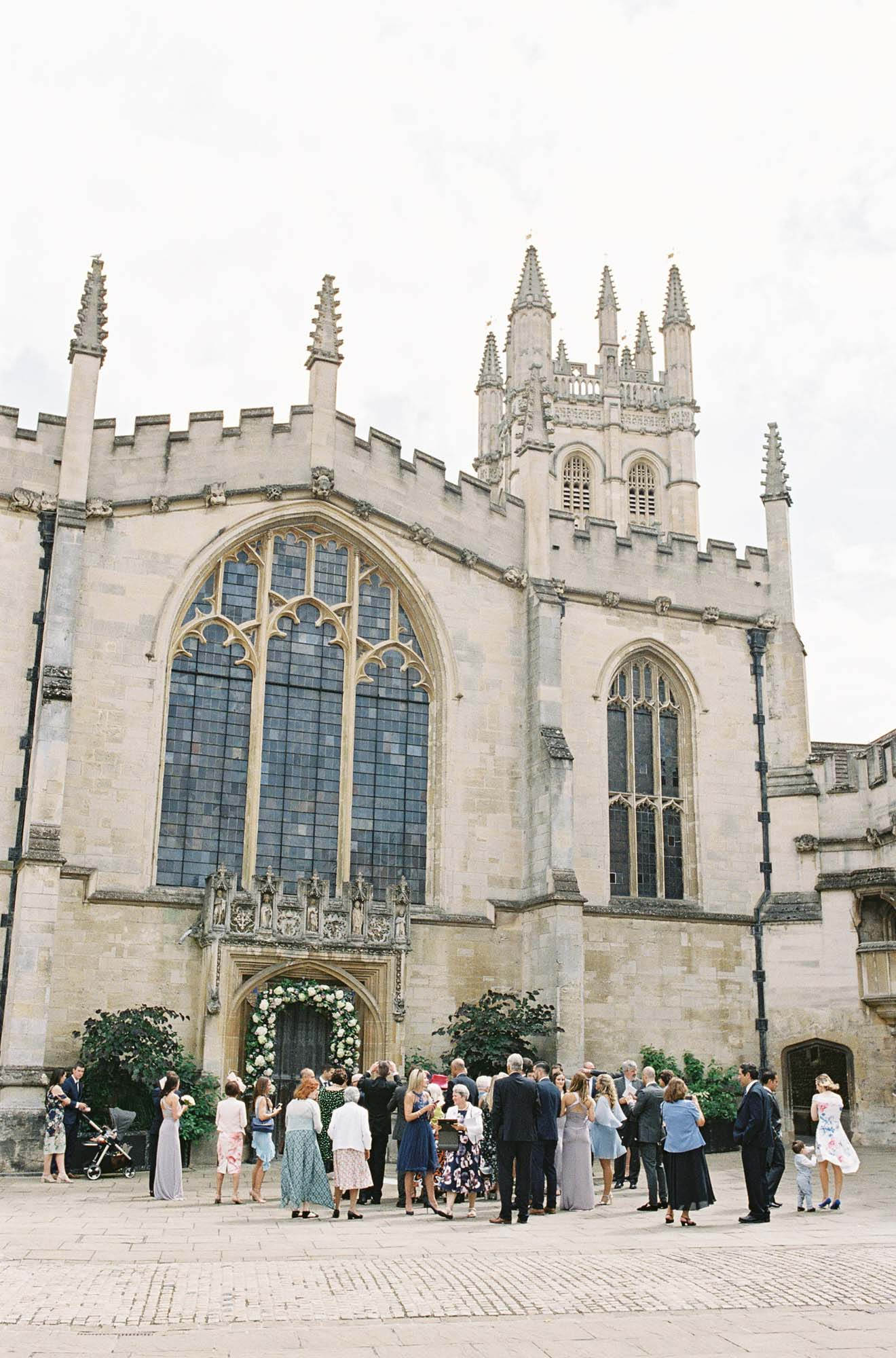 Magdalen College Chapel with wedding guests outside captured by film wedding photographer Camilla Arnhold