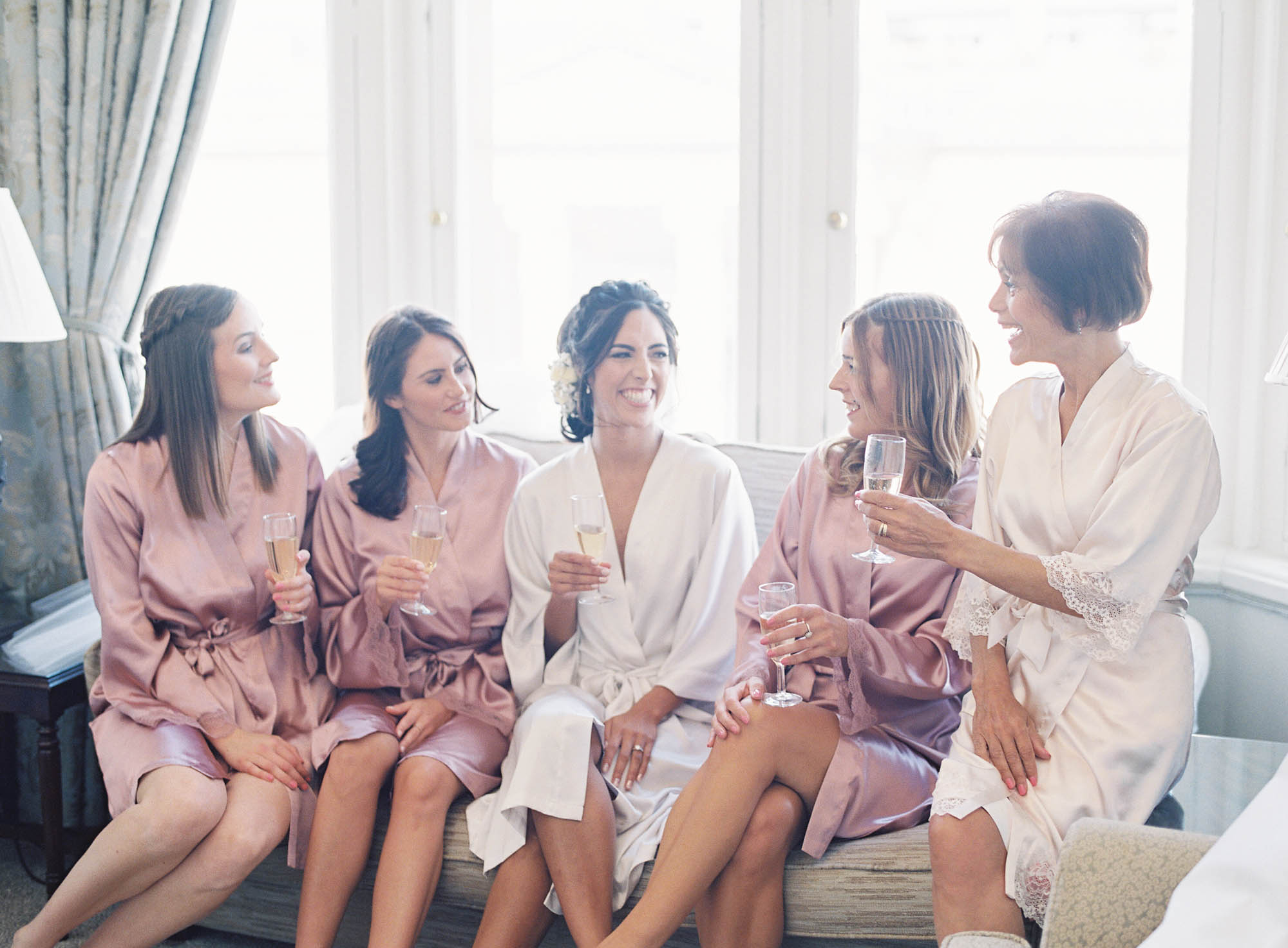 Bride and bridesmaids chatting and laughing with champagne in The Randolph Hotel