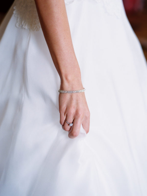 Bride's hand gathering up her Suzanne Neville wedding dress