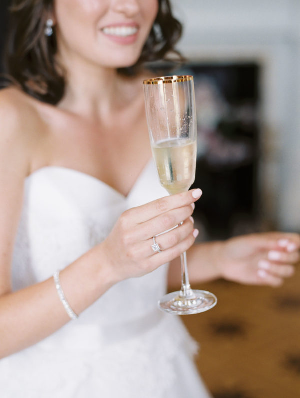 Bride drinking champagne in the bridal suite at Stansted House