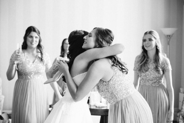 Bride hugging bridesmaid and smiling