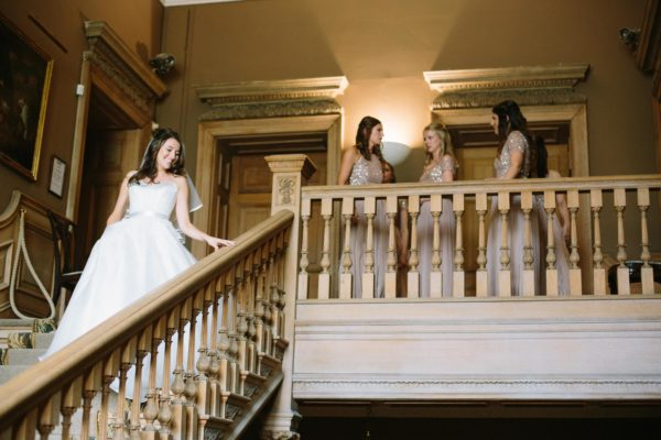 Elegant bride coming down the staircase at Stansted House