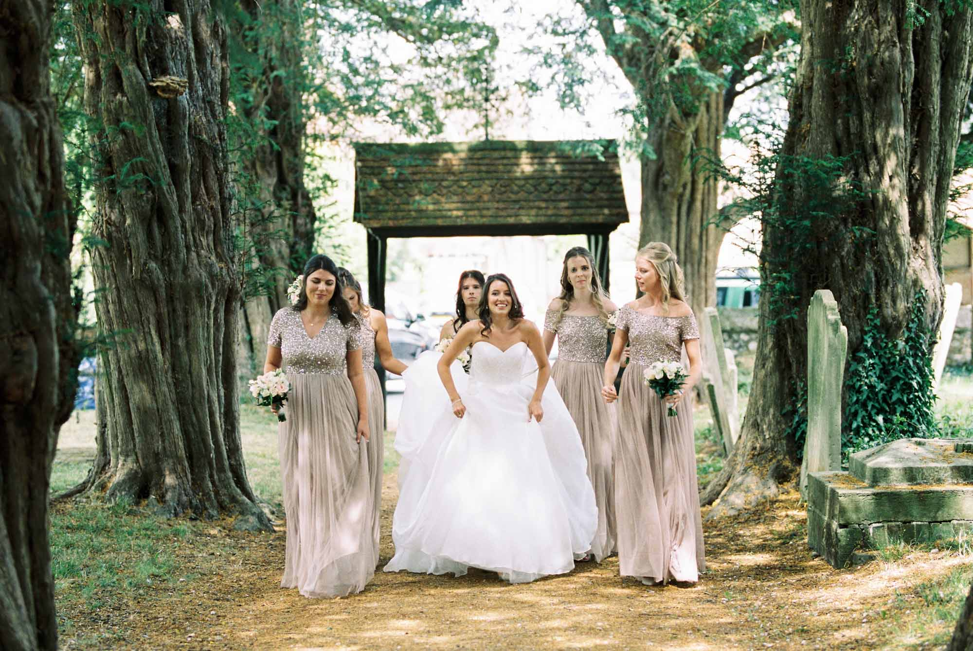 Bride walking with bridesmaids up the path of the church before wedding ceremony