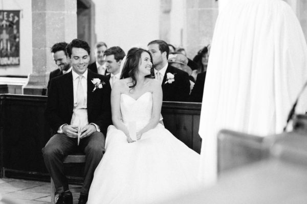Bride and groom smiling and laughing during church wedding service