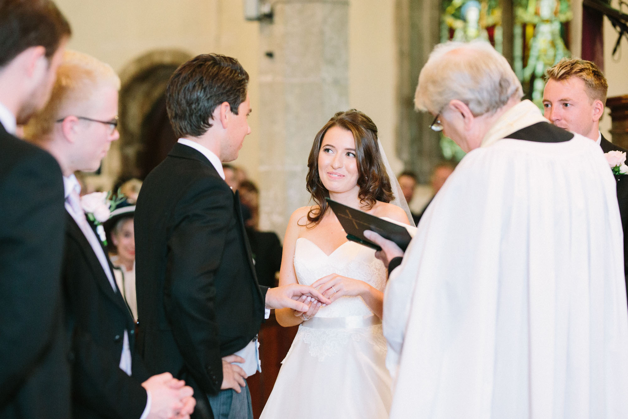 Bride and groom exchanging rings during wedding service at Westbourne Church