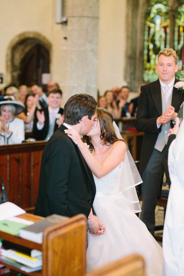 Bride and groom having first kiss in church