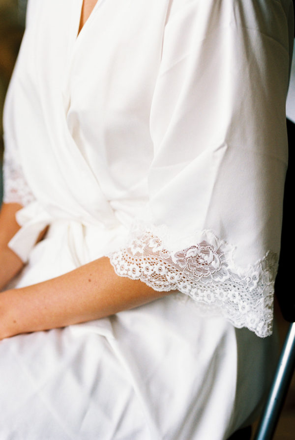 Film wedding photography. White silk and lace bridal dressing gown on wedding morning.