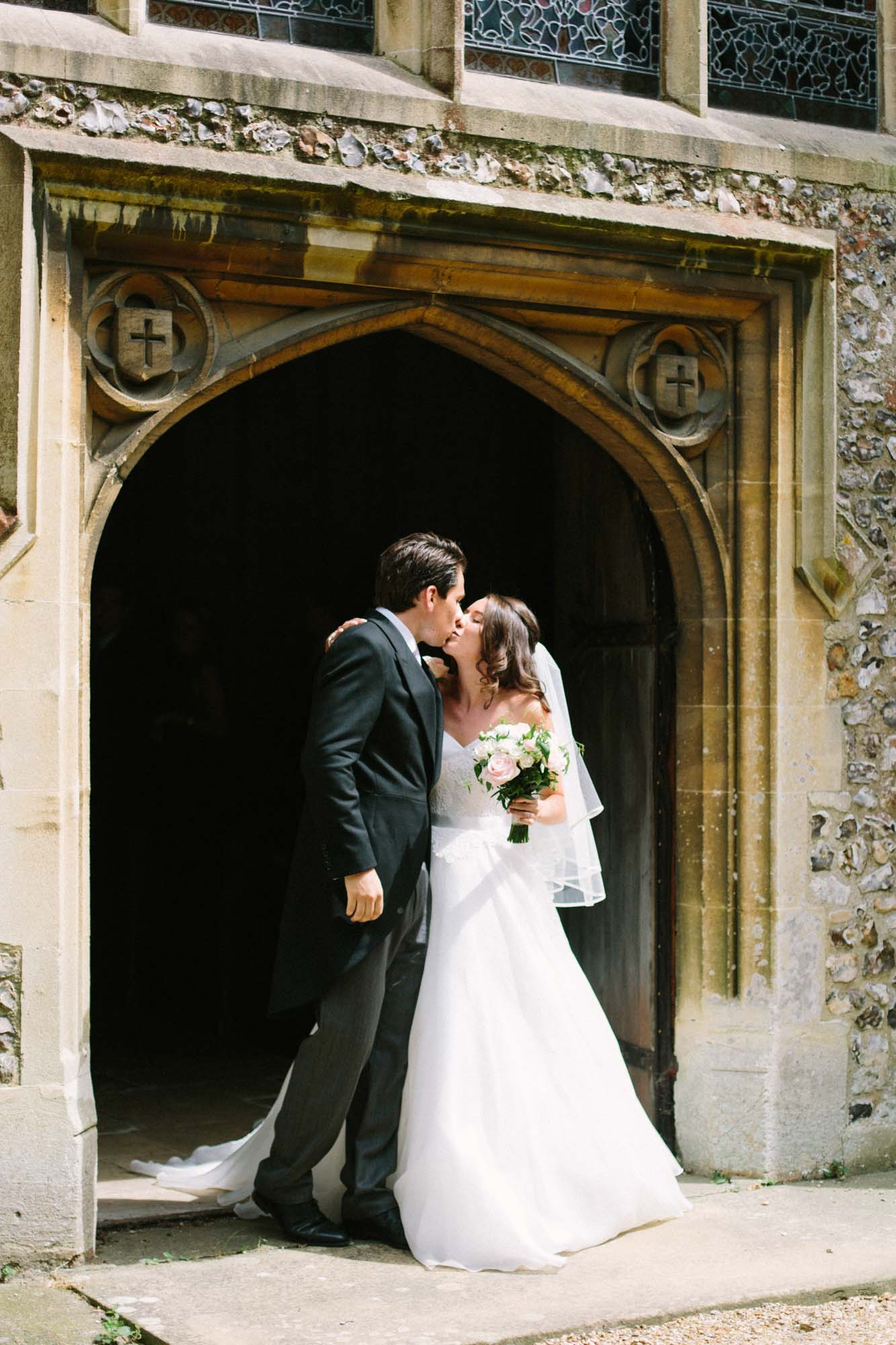 Bride and groom kissing in porch of church in Westbourne