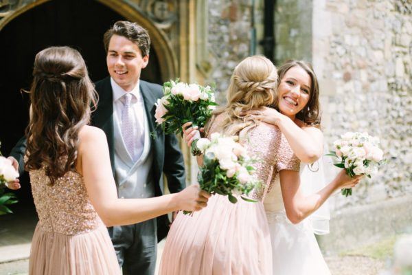 Bride and groom higging bridesmaids outside church after wedding ceremony