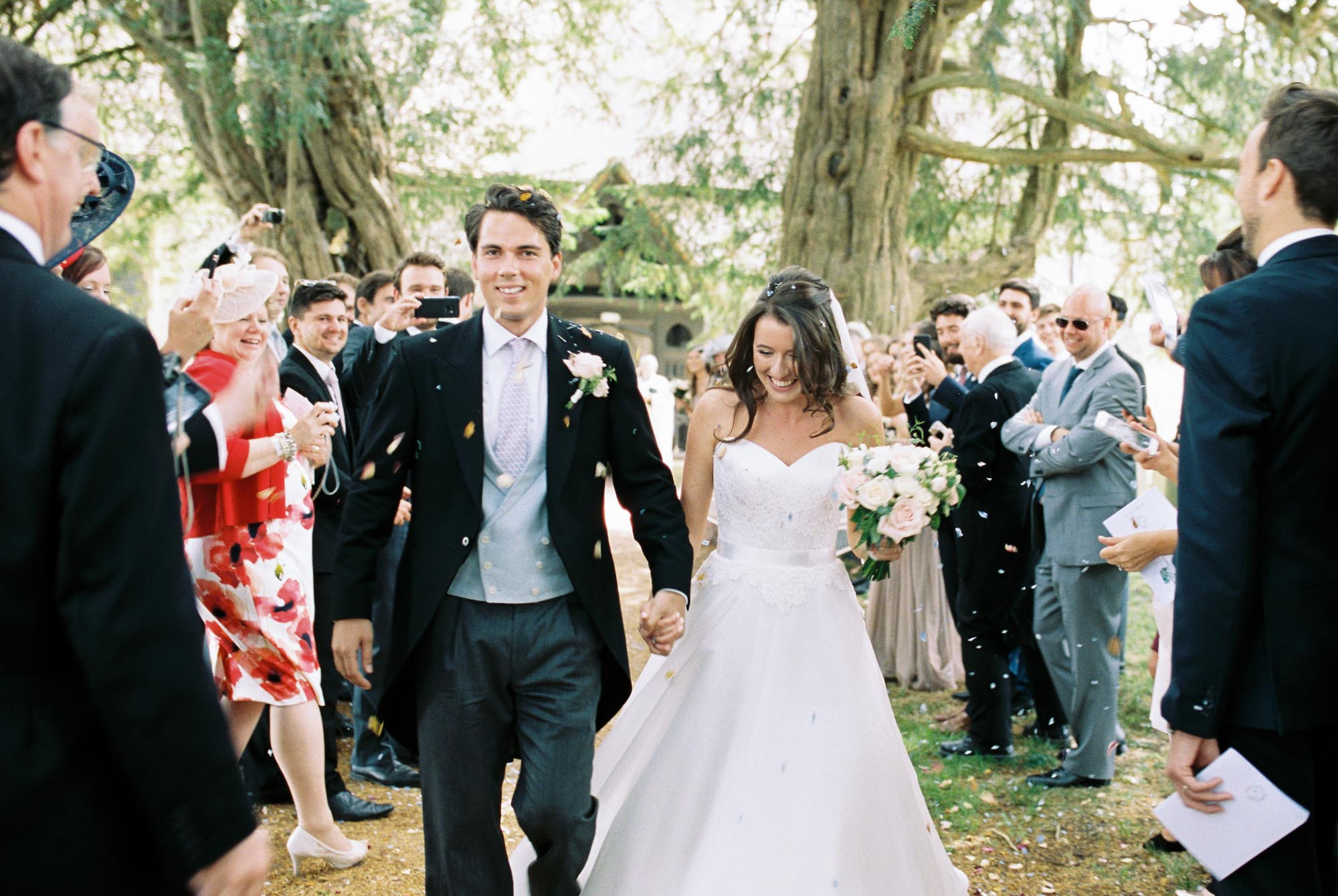 Bride and groom walking through confetti and leaving church