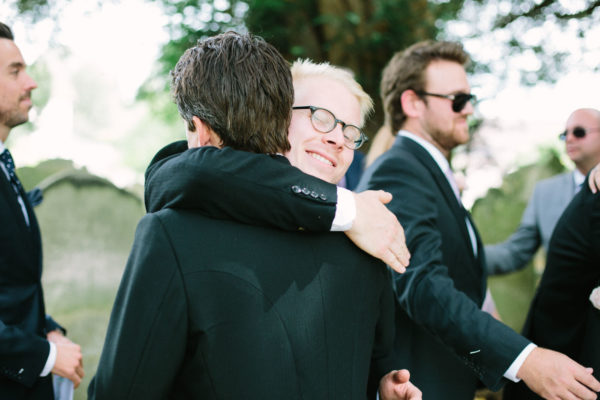 Groomsman hugging groom after wedding ceremony