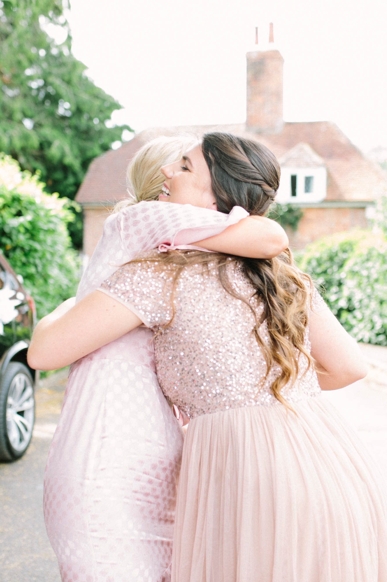 Bridesmaid in blush sequin dress hugging a wedding guest