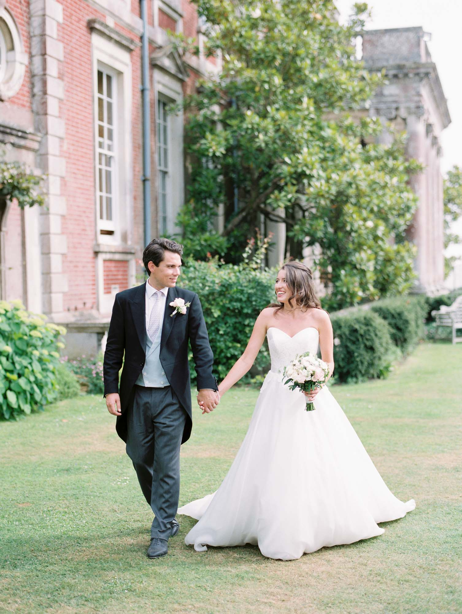 Bride and groom walking hand in hand in the ground of Stansted House
