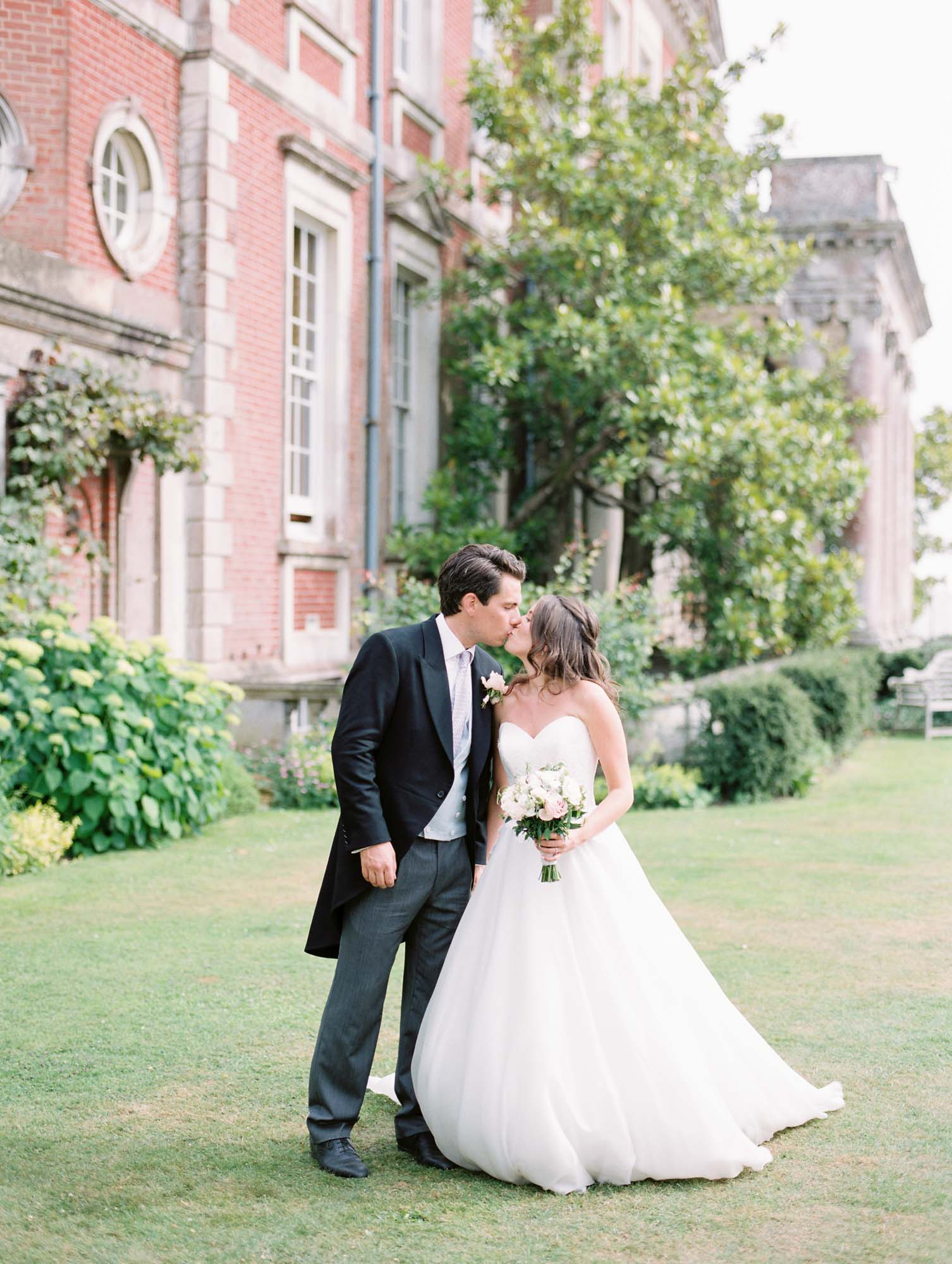 Bride and groom kissing on the lawn of Stansted House