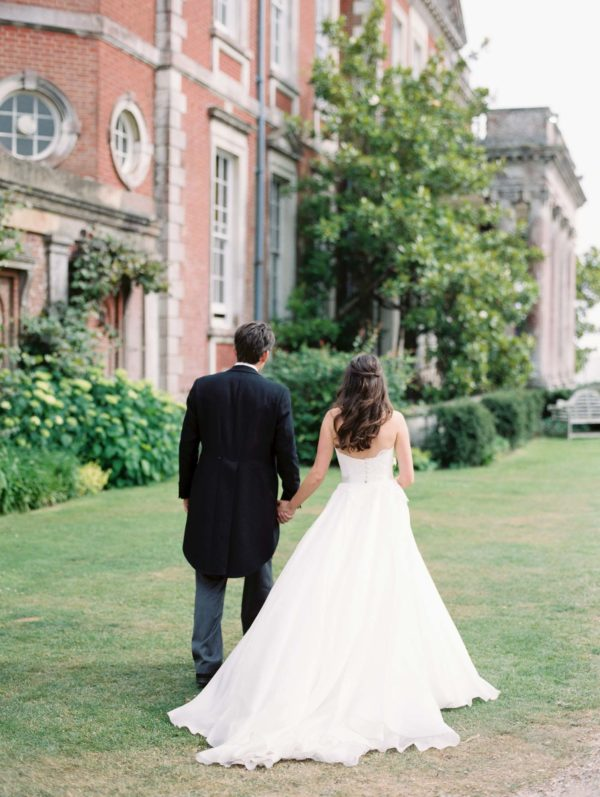 Bride and groom walking hand in hand at their Stansted House wedding