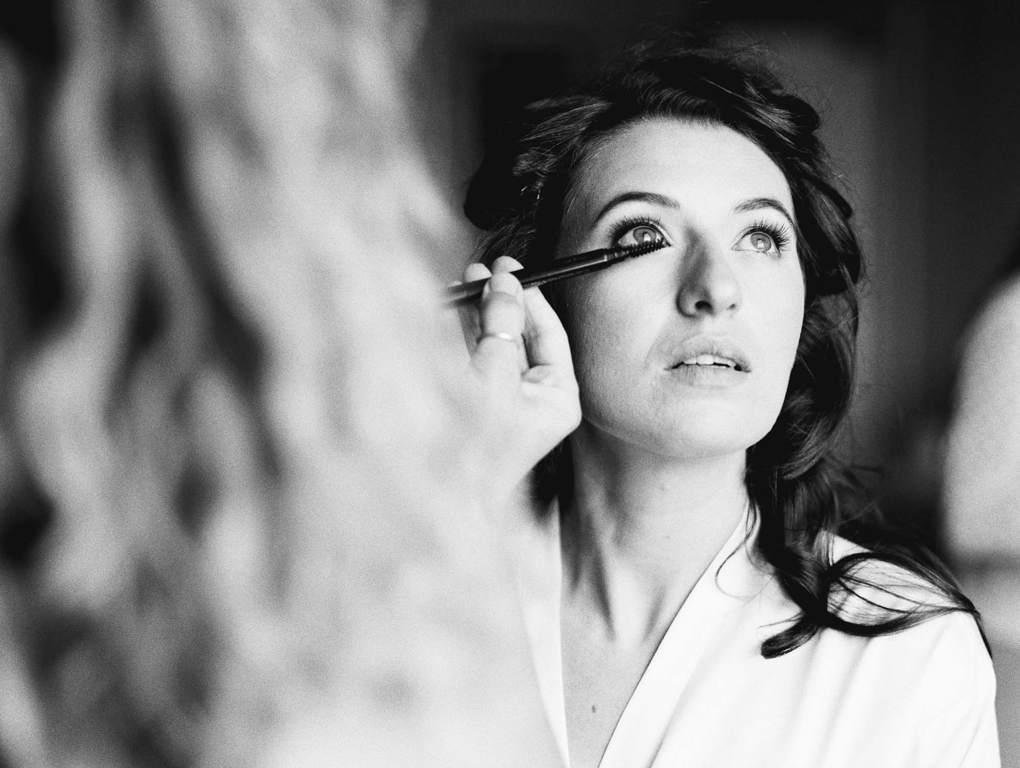 Black and white photograph of bride having her wedding make up done at Stansted House