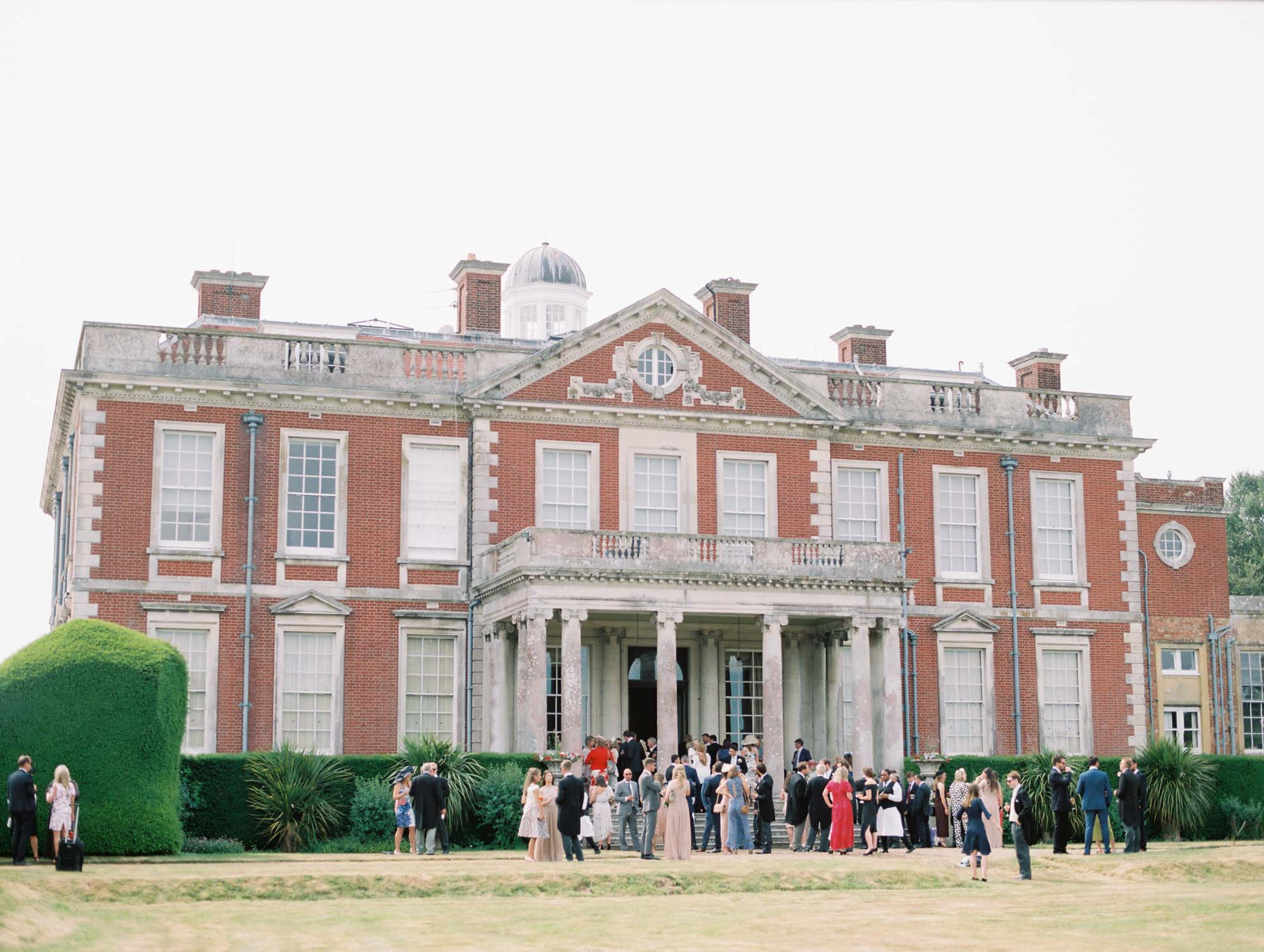 Wedding guests mingling at the rear of Stansted House wedding