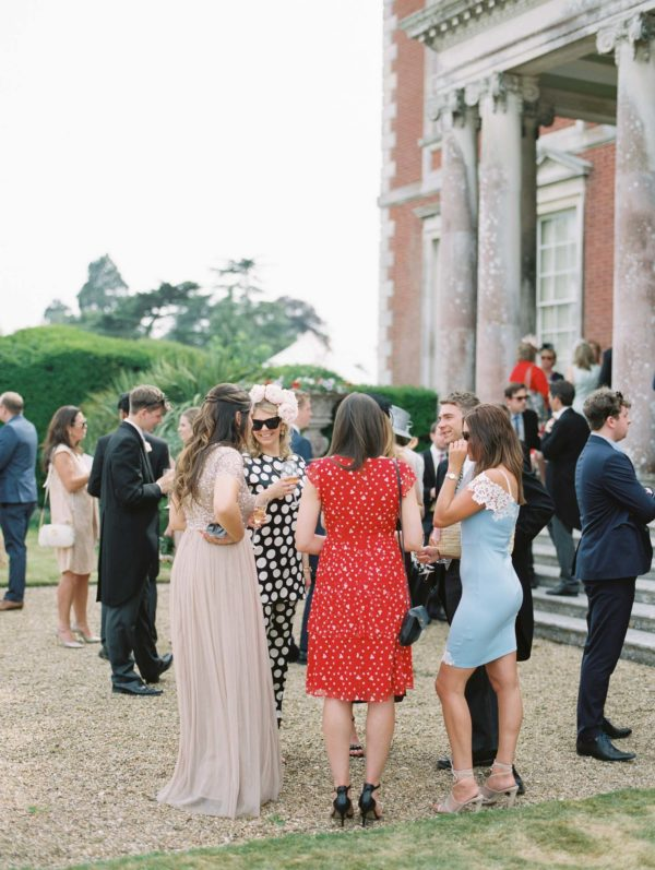 Stylish wedding guests outside Stansted House