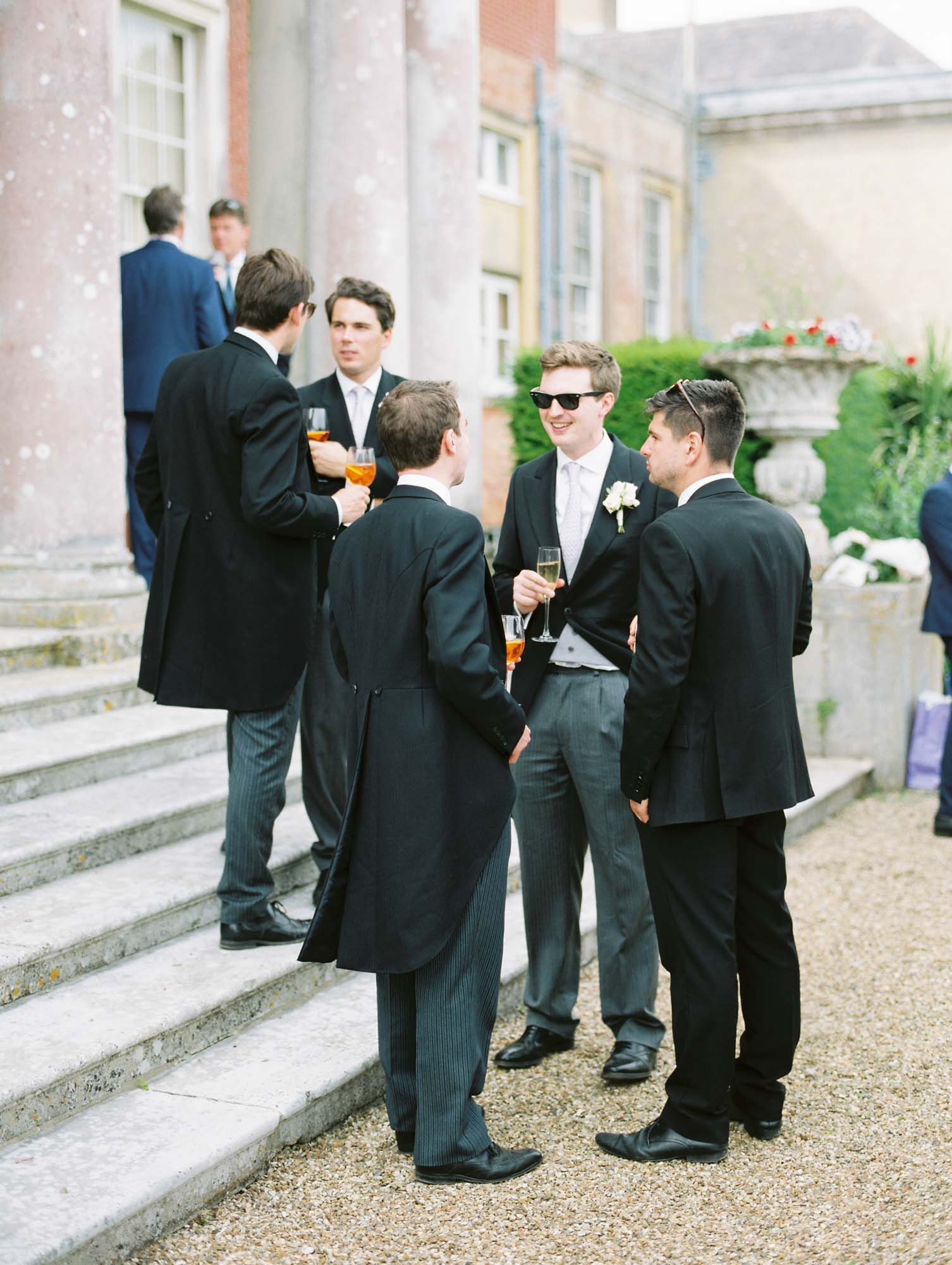 Elegant male wedding guests talking on the steps of Stansted House