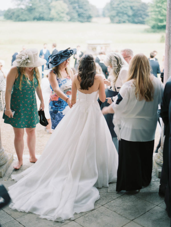 Photograph of bride chatting to wedding guests from behind on the steps of Stansted House