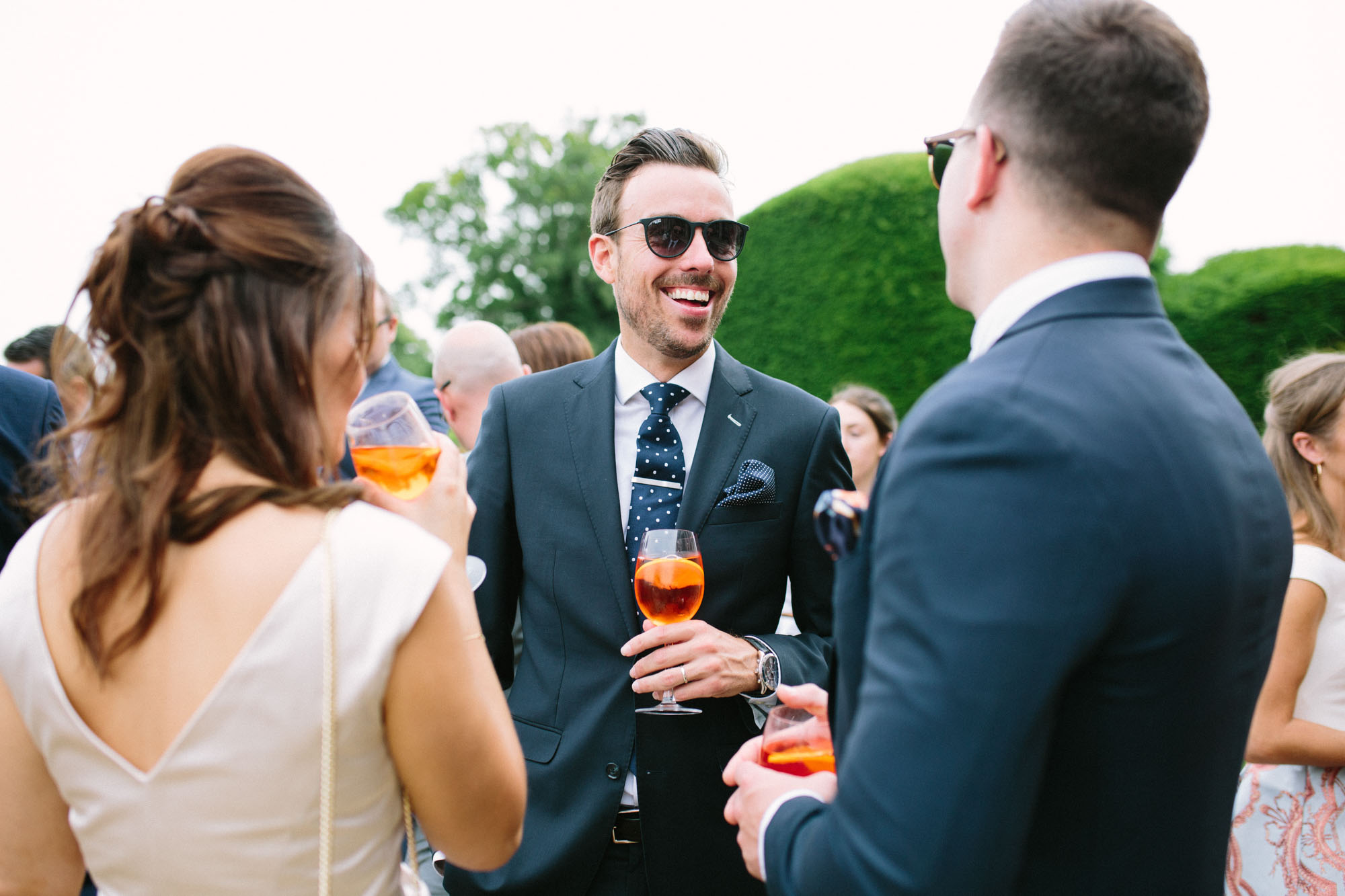 wedding guests laughing and drinking Aperol at Stansted House wedding