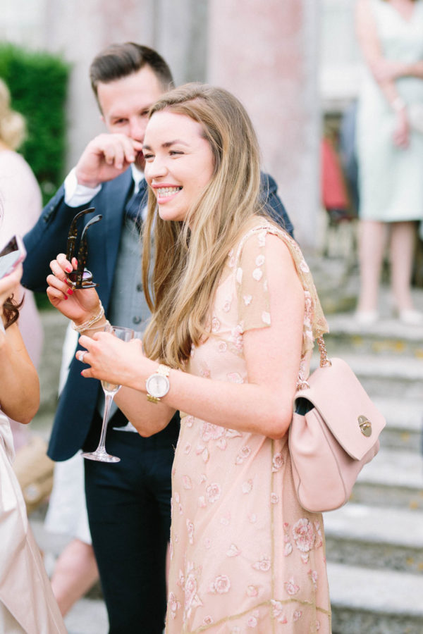Wedding guest in peach dress laughing during wedding reception