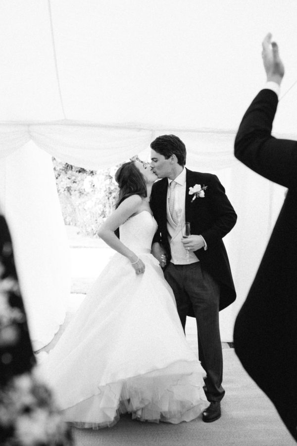 Black and white photograph of bride and groom kissing in the entrance of their marquee at Stansted House wedding