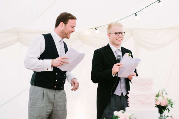 Best men delivering funny speech in wedding marquee