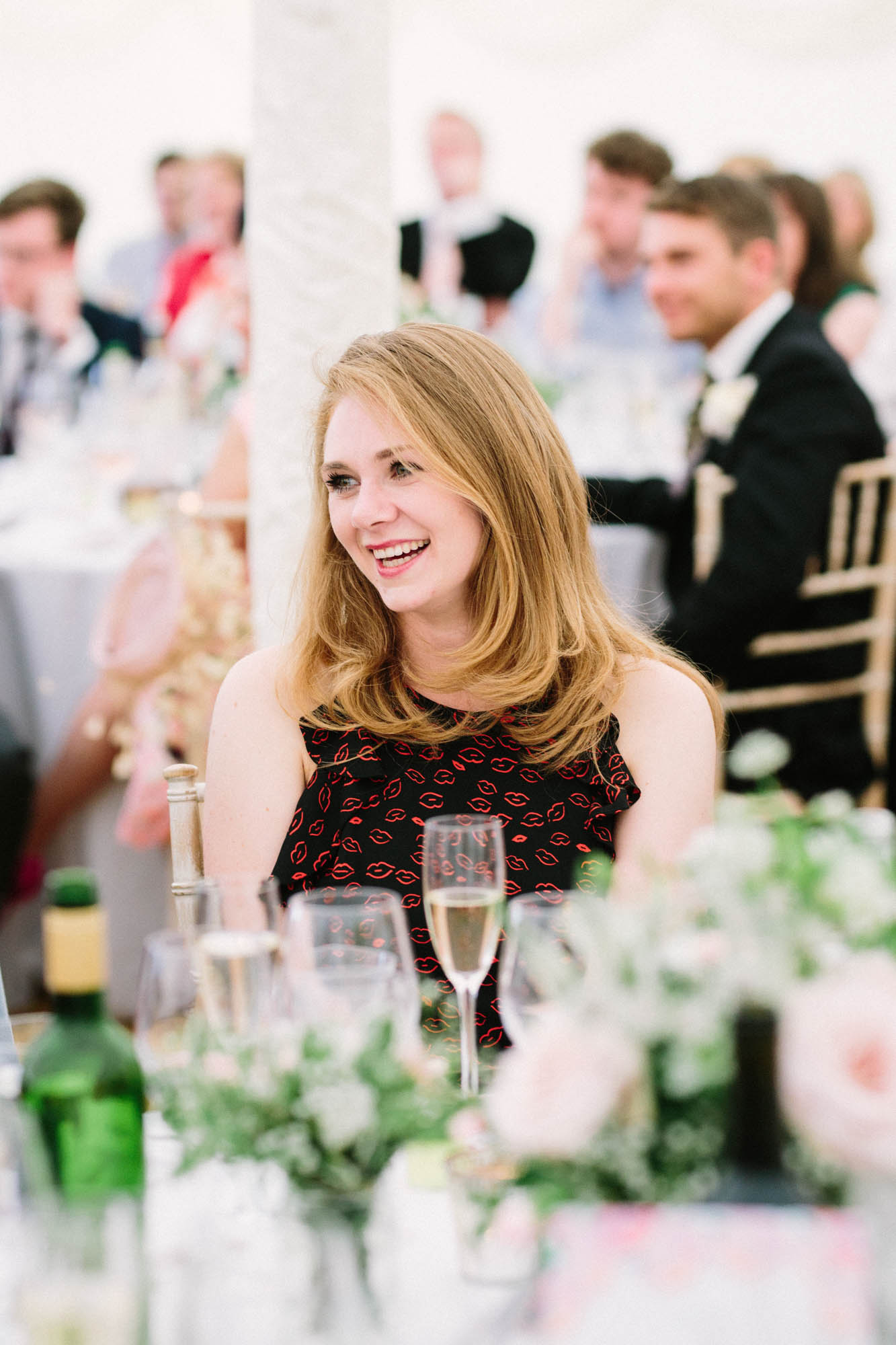 Natural wedding photography of wedding guest laughing during speeches