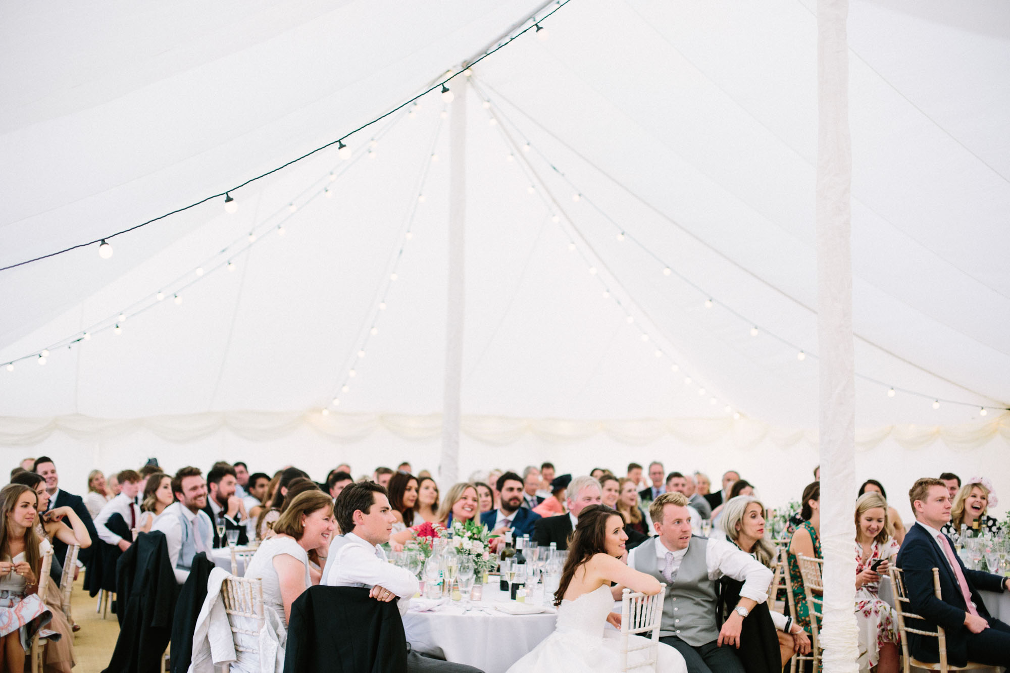 Whole marquee of wedding guests laughing at speeches