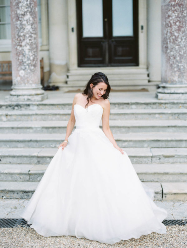 Bride holding the skirt of her Suzanne Neville wedding dress of the steps of Stansted House wedding