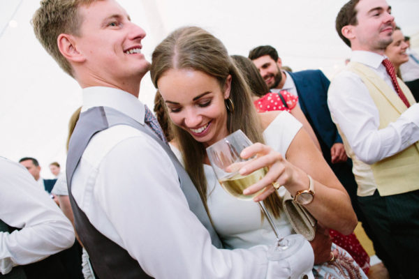Wedding guests dancing holding a glass of white wine
