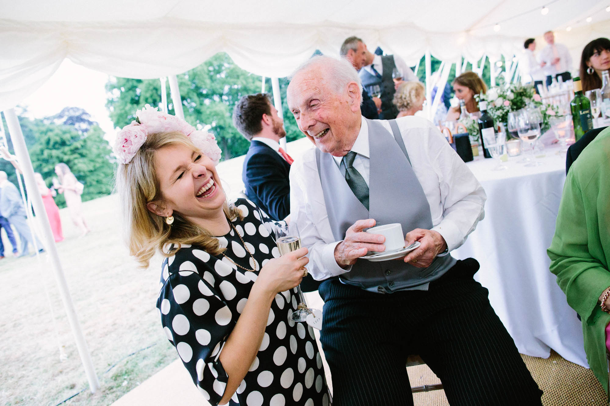 Old man and lady laughing and drinking tea in the marquee at Stansted House