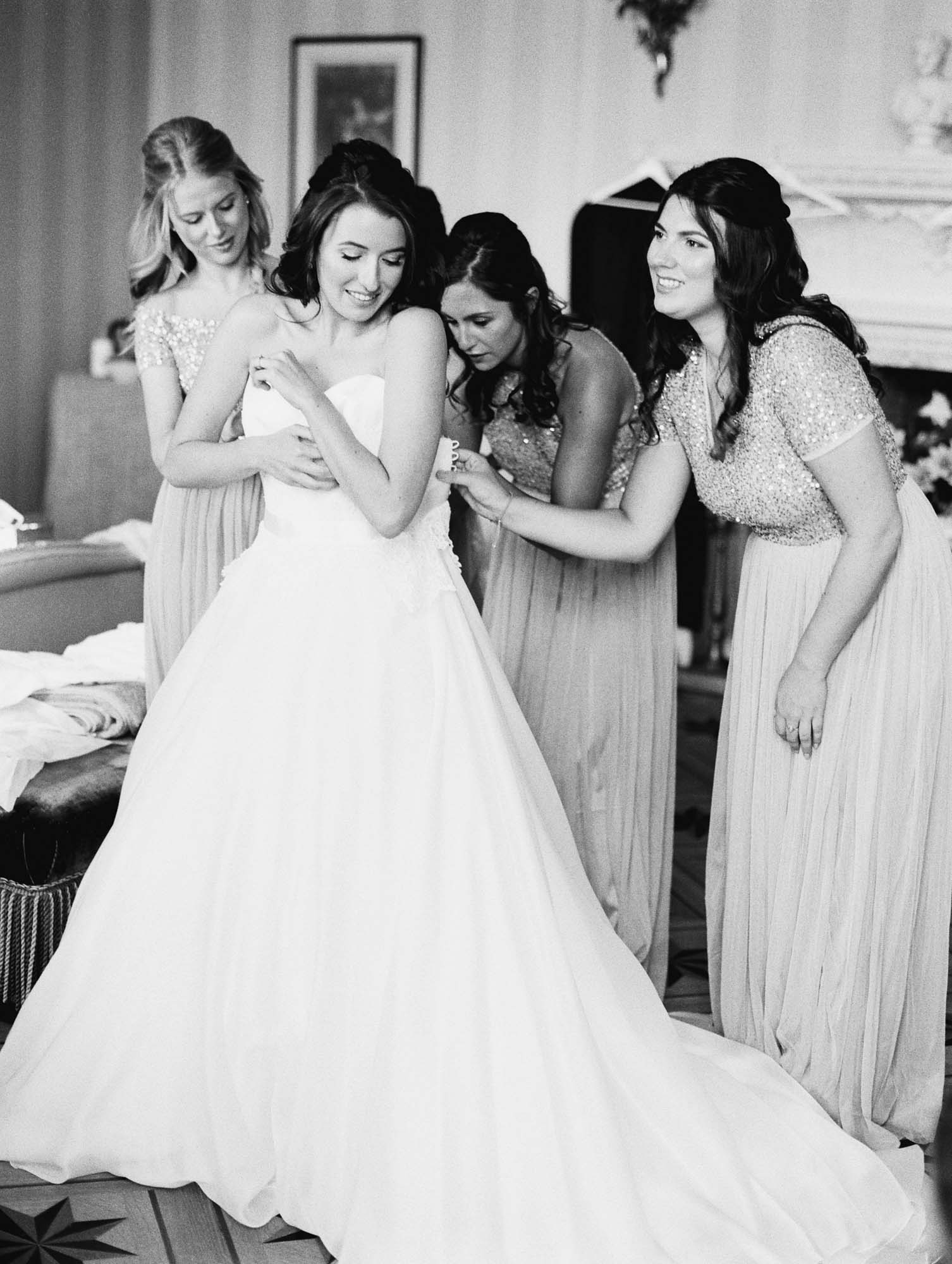 Bride putting on wedding dress with bridesmaids at Stansted House