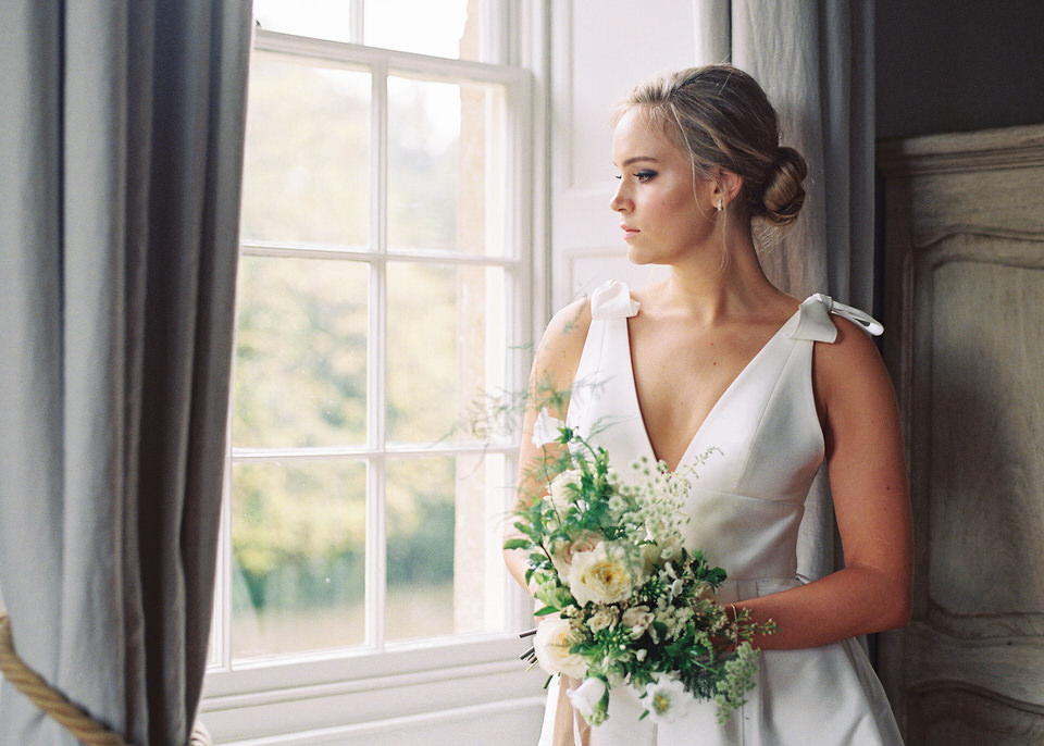 Bride looking out of window holding bouquet at Thorpe Manor, Oxfordshire