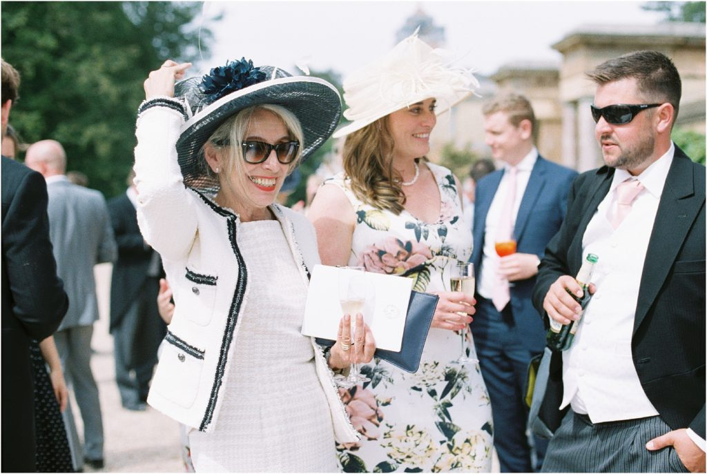Mother of the bride holding hat on wedding day at Stansted House, West Sussex