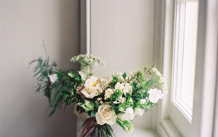 Loosely structured wedding bouquet of blush, cream and green on windowsill at Thorpe Manor luxury wedding venue