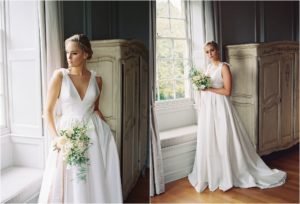 Bride standing by the window of the Thorpe Manor bridal suite wearing wedding dress and holding bouquet