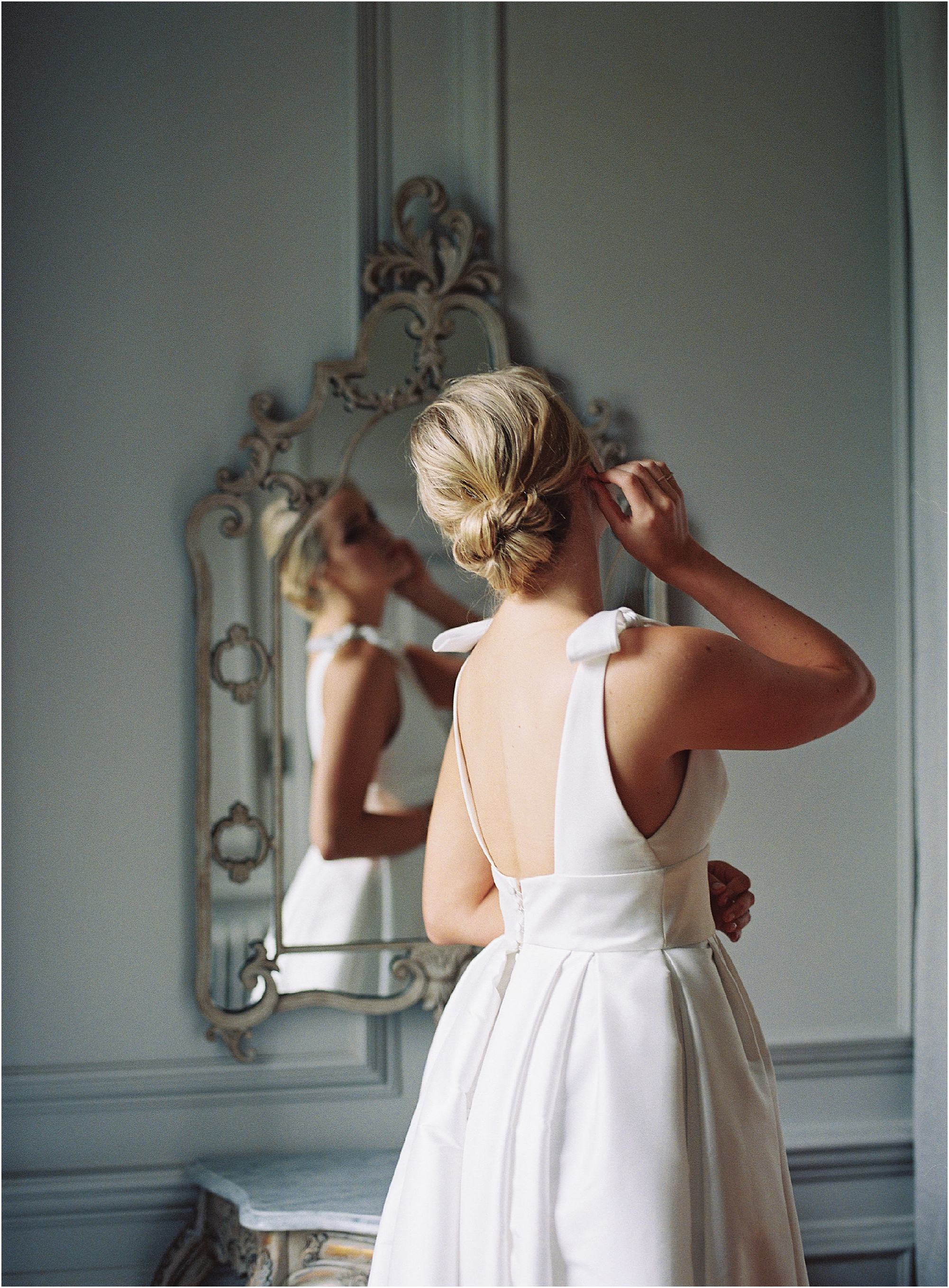 View of bride looking in the mirror on the morning of her Thorpe Manor wedding