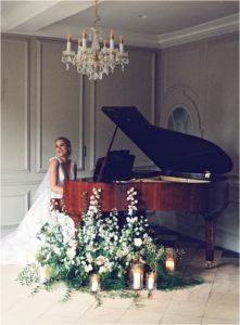 Elegant bride sitting at the grand piano at Thorpe Manor, Oxfordshire