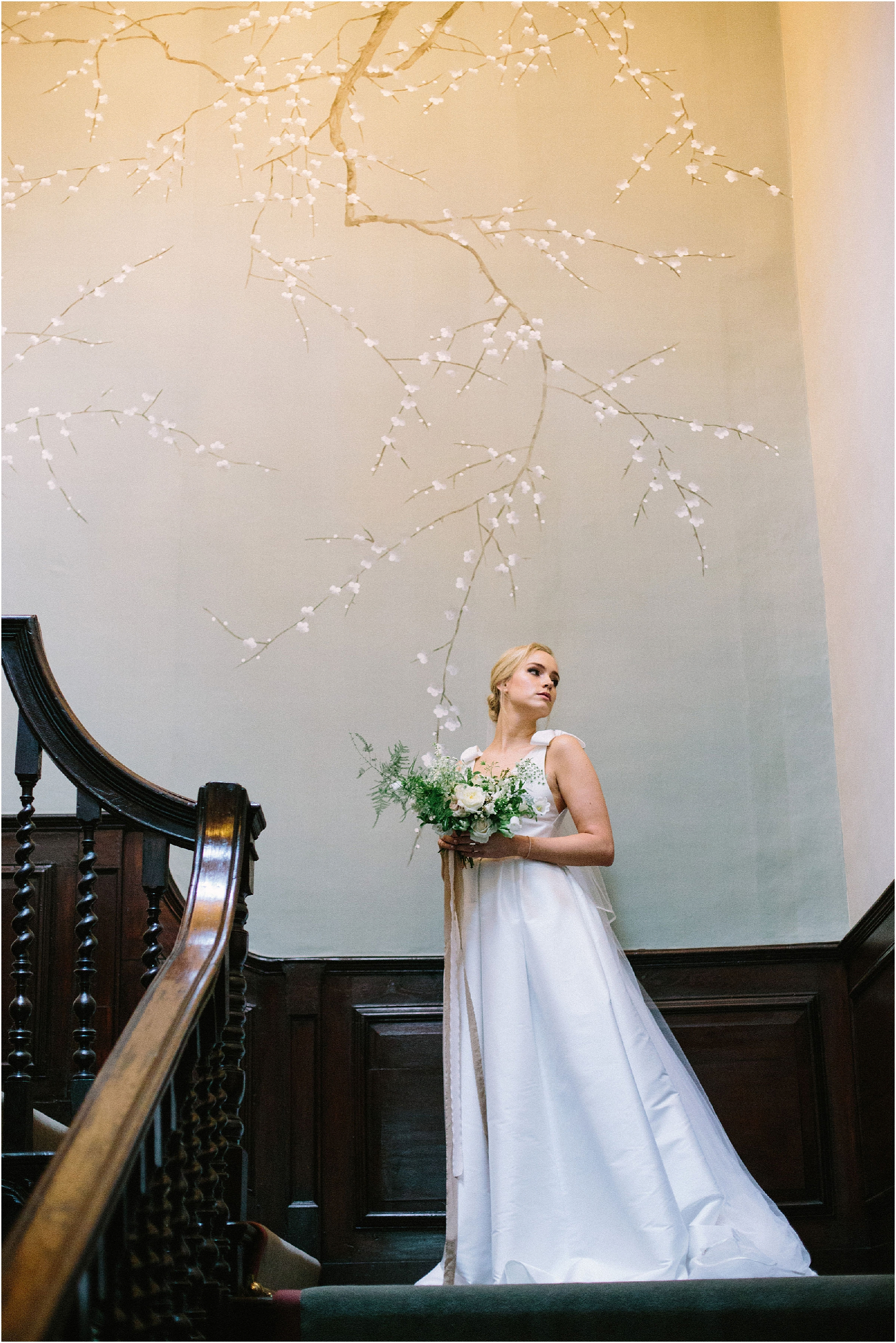 Bride standing on the staircase in front of silk hand painted wallpaper at Thorpe Manor