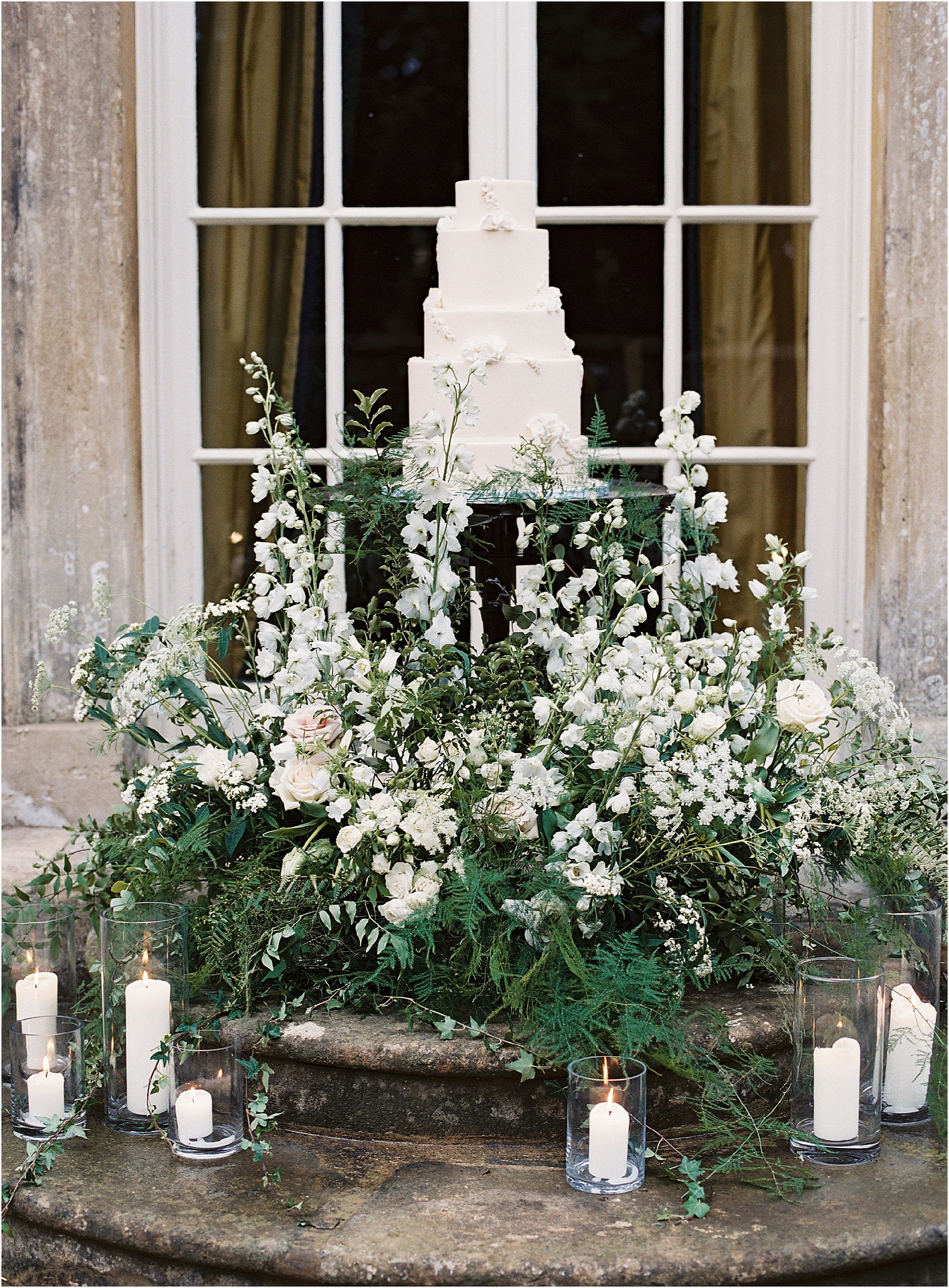 Cream five tier wedding cake amongst floral display on the steps of Thorpe Manor