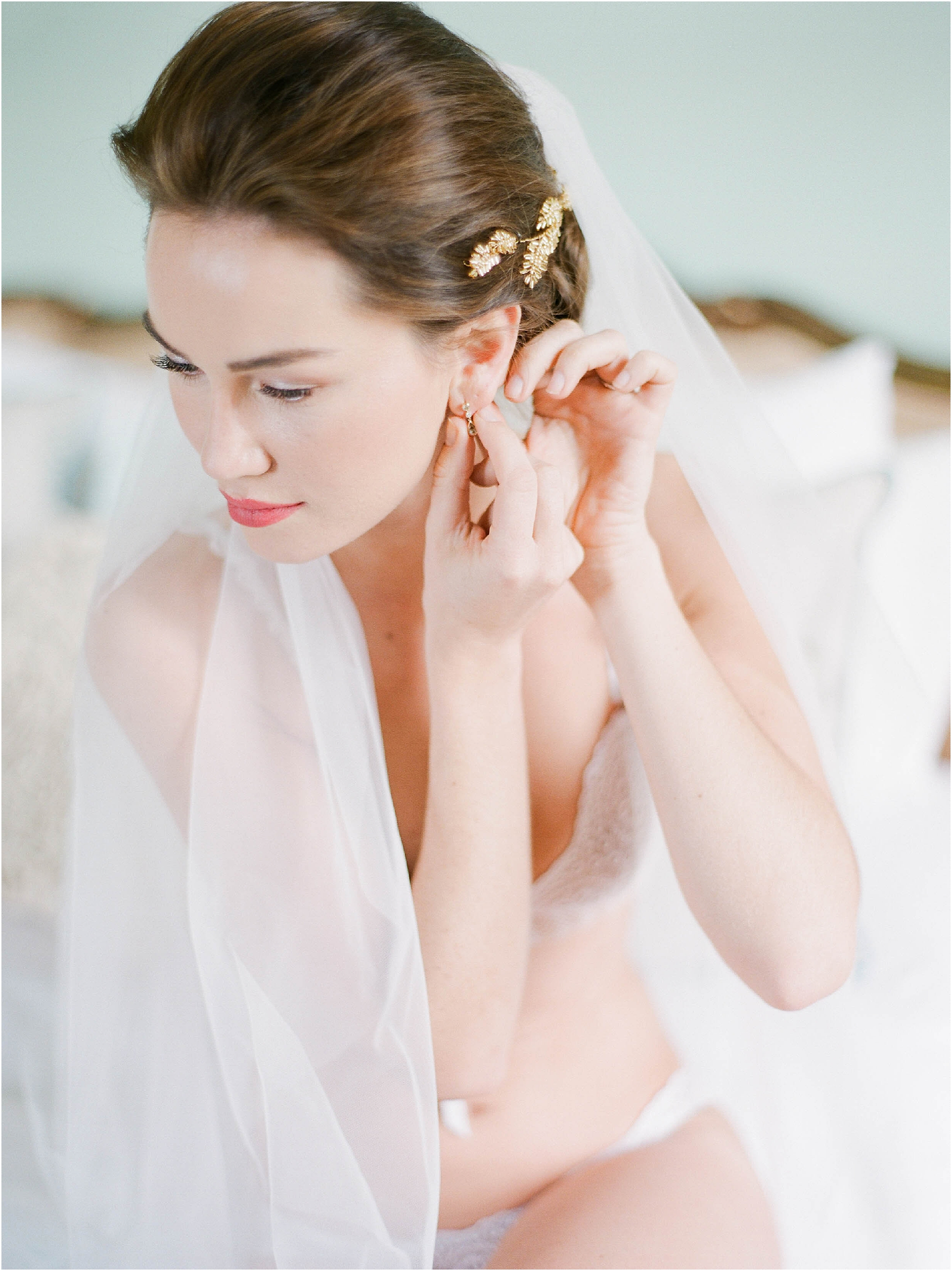 Bride putting in earrings on wedding morning at Hill Place Hampshire