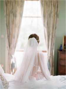 Bride looking out of window at Hill Place