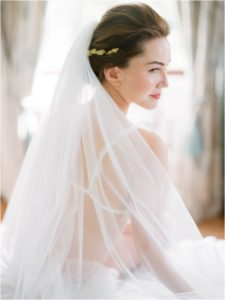 Bride looking over shoulder and smiling in boudoir photograph