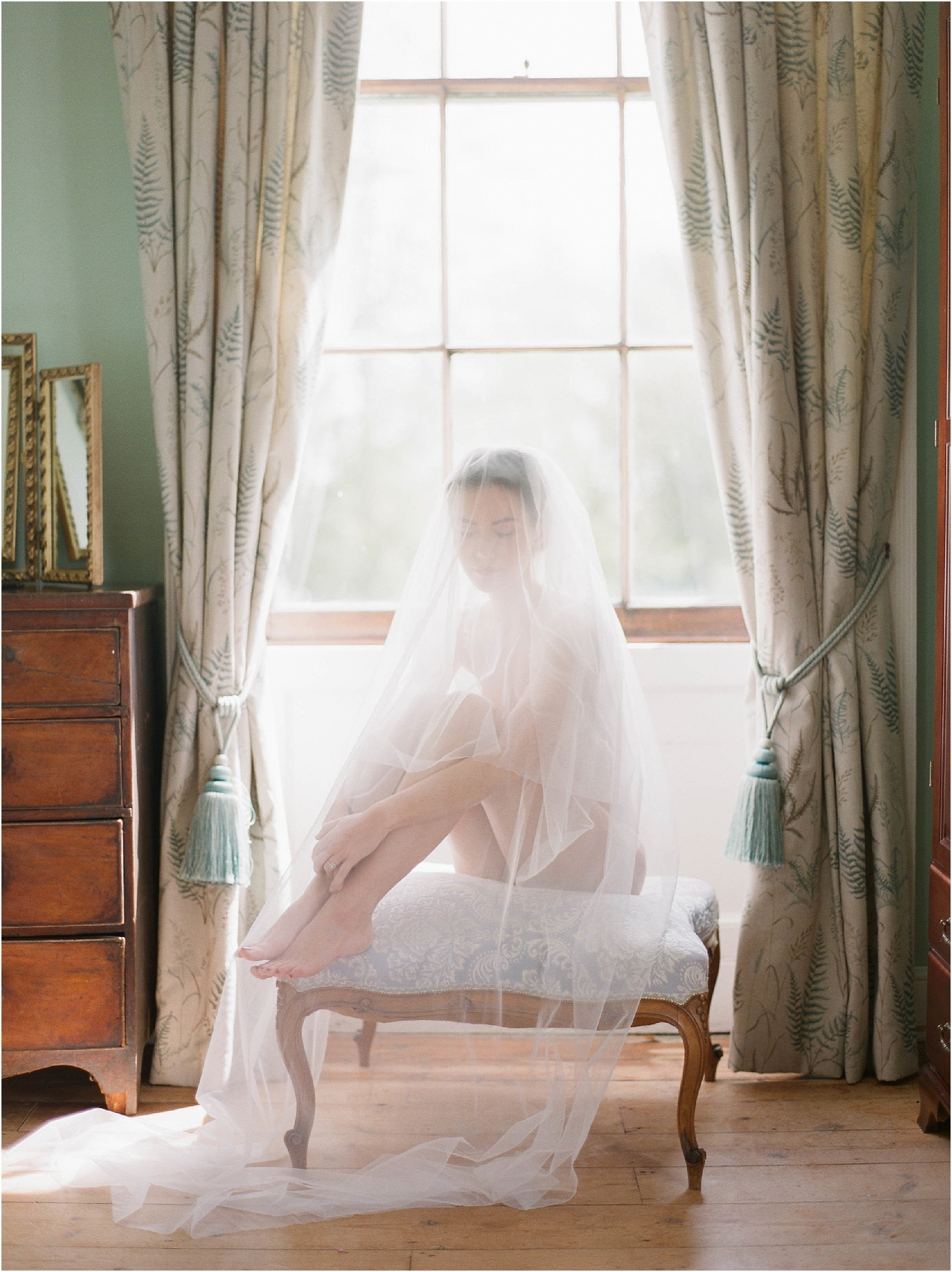 Bride sitting on stool with veil over her