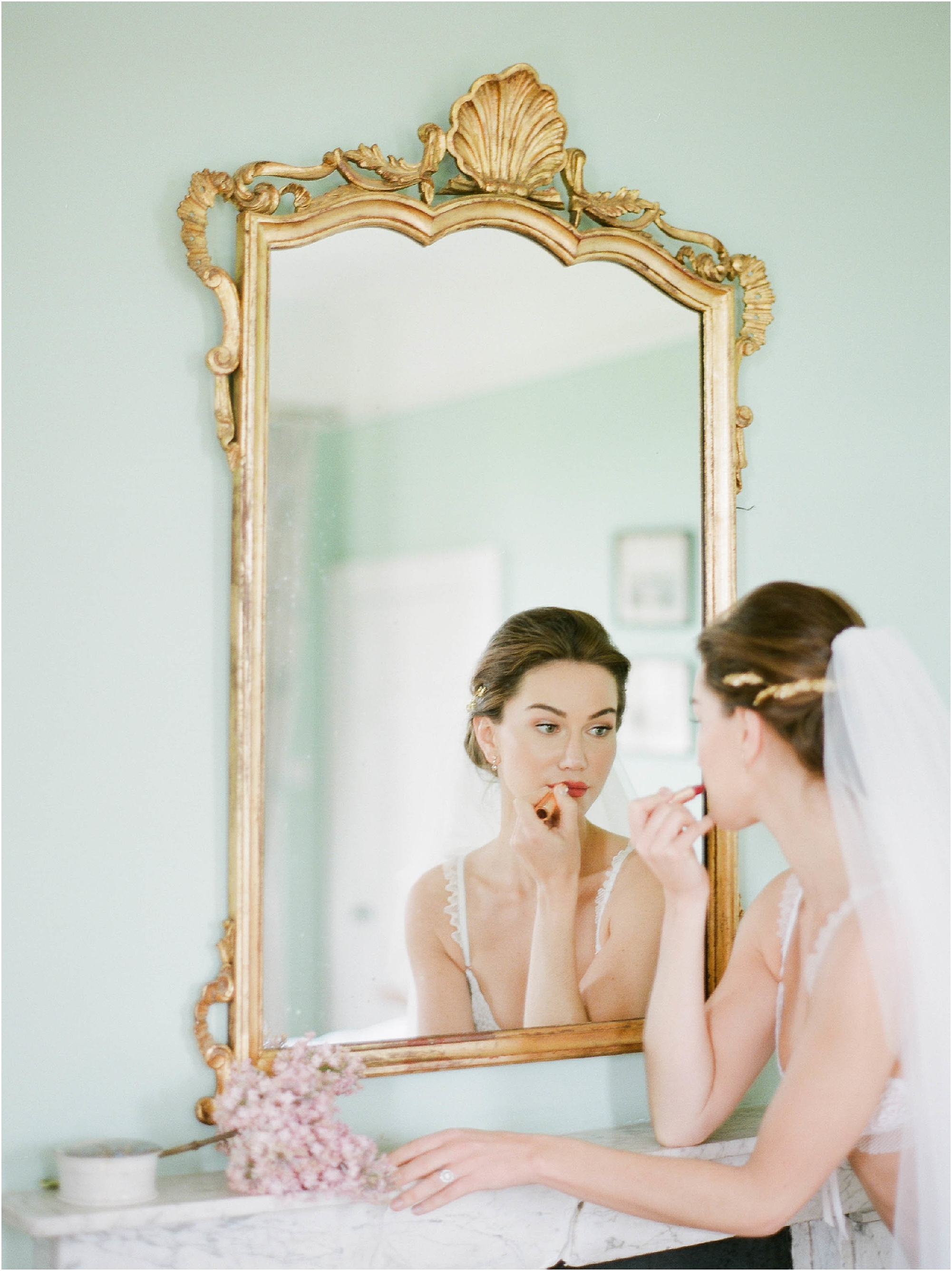 Bride applying lipstick in mirror at Hill Place