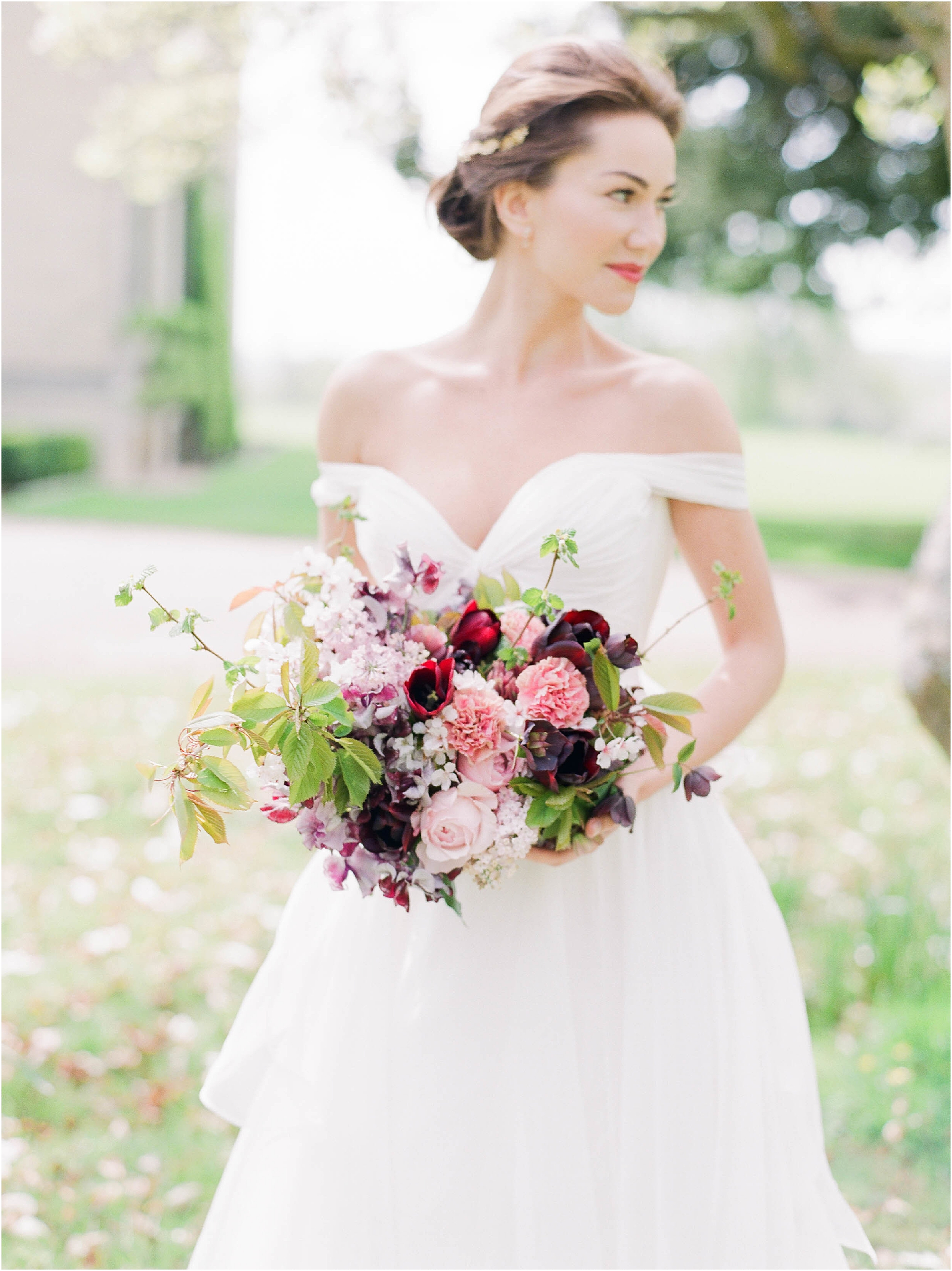 Bride holding bouquet of maroon and pink