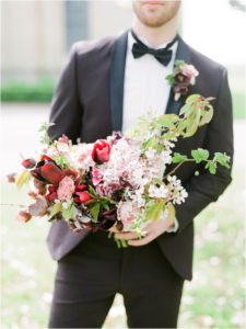 Groom holding bouquet by Martha and the meadow