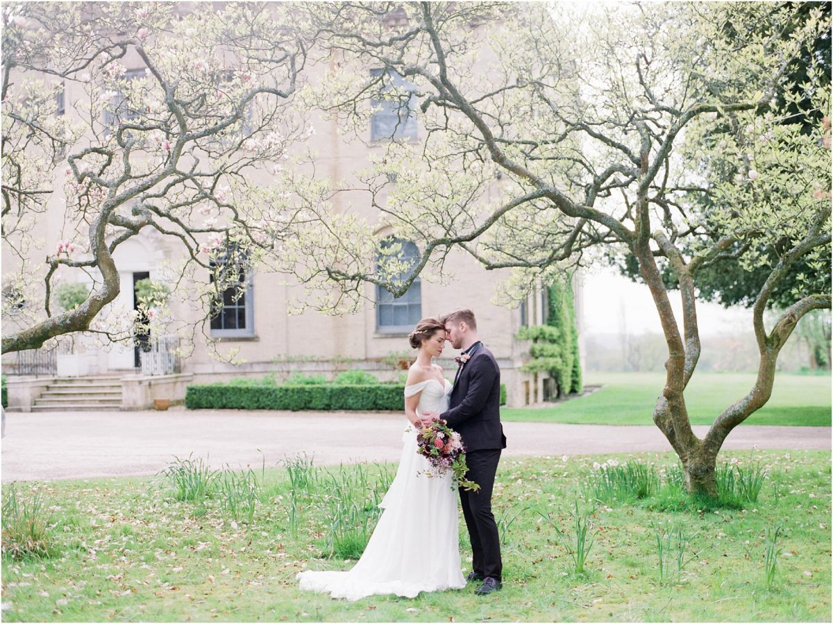 Bride and groom standing under magnolia tree
